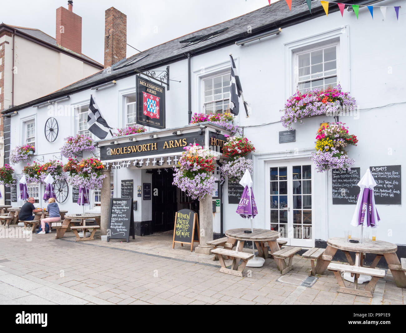 The Molesworth Arms pub and hotel in Wadebridge Cornwall UK with pretty window boxes and hanging baskets full of flowers in summer - Stock Image