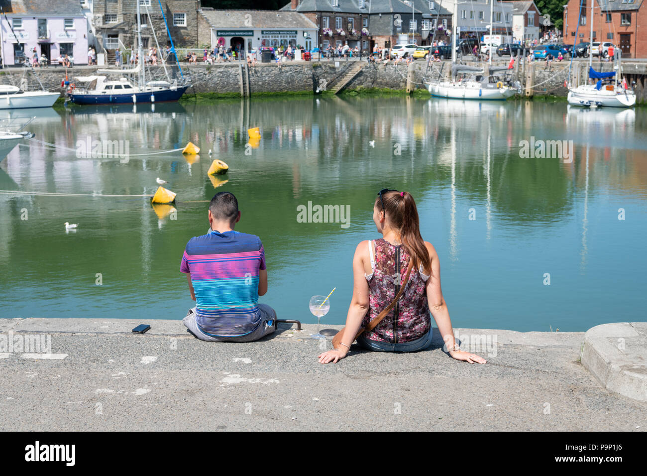 A young man and woman sitting on the quay at Padstow Harbour Cornwall UK enjoying a drink on a hot summer day - Stock Image