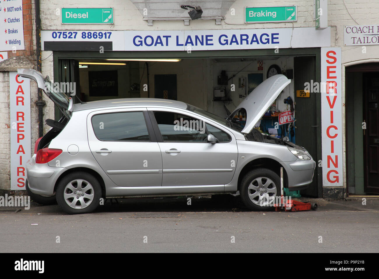 A car being fixed at a small garage at Goat Lane, Basingstoke. - Stock Image
