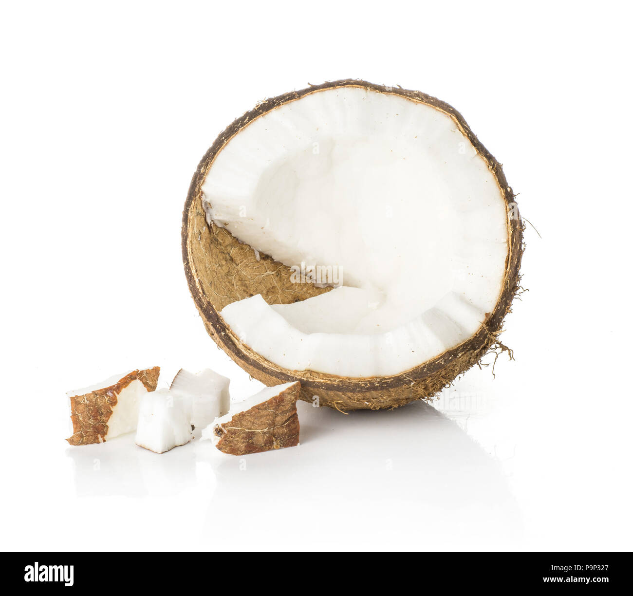 One coconut half with three pieces isolated on white background brown fibrous shell with milk meat - Stock Image