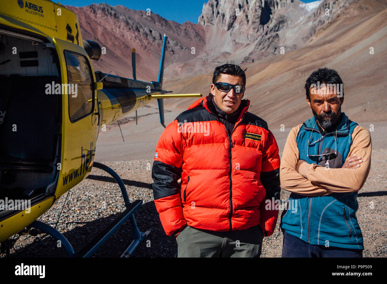 Park rangers stand outside a helicopter in Aconcagua Provincial Park, Argentina. Helicopters play a major role in delivering supplies and conducting rescues in the park. - Stock Image