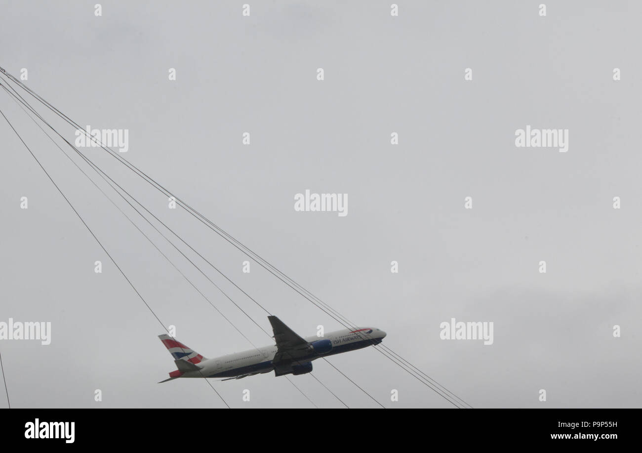 The Boeing 777-200 of British Airways pictured through electrical wires as it takes off from Heathrow airport, London, UK - Stock Image