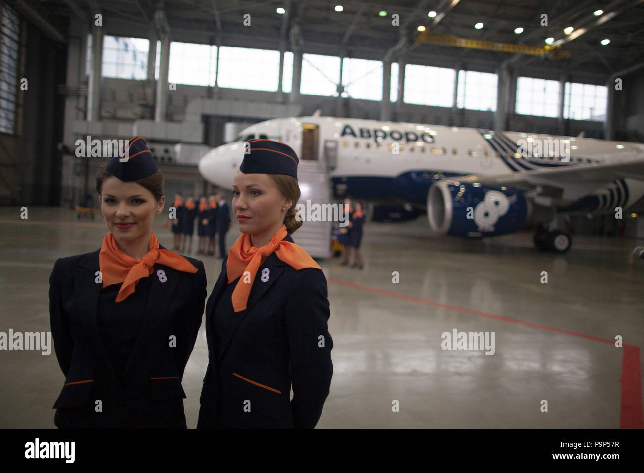 Two flight attendants of Aurora airline stand near the airline's first Airbus A319 civil jet airplane during the official presentation at Sheremetyevo - Stock Image