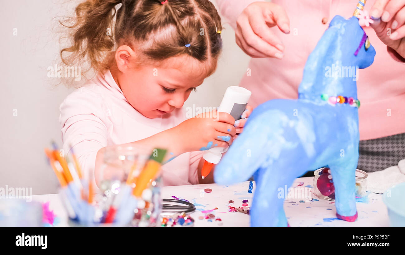 Mother And Daughter Decorating Paper Mache Unicorn With Jewels And