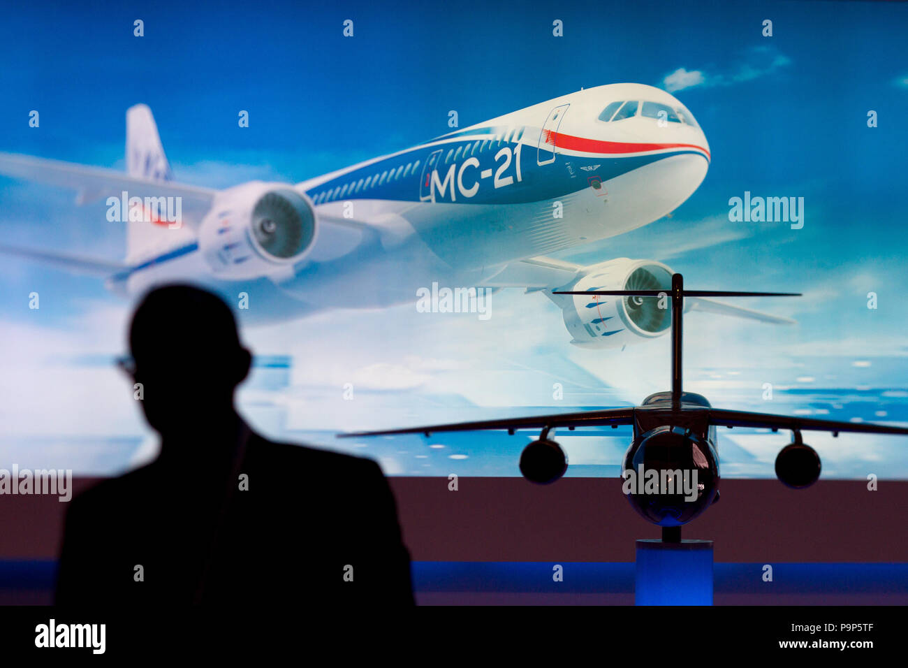 A visitor to the show silhouetted against the image of Irkut MC-21 civil aircraft at Farnborough International Airshow, UK Stock Photo