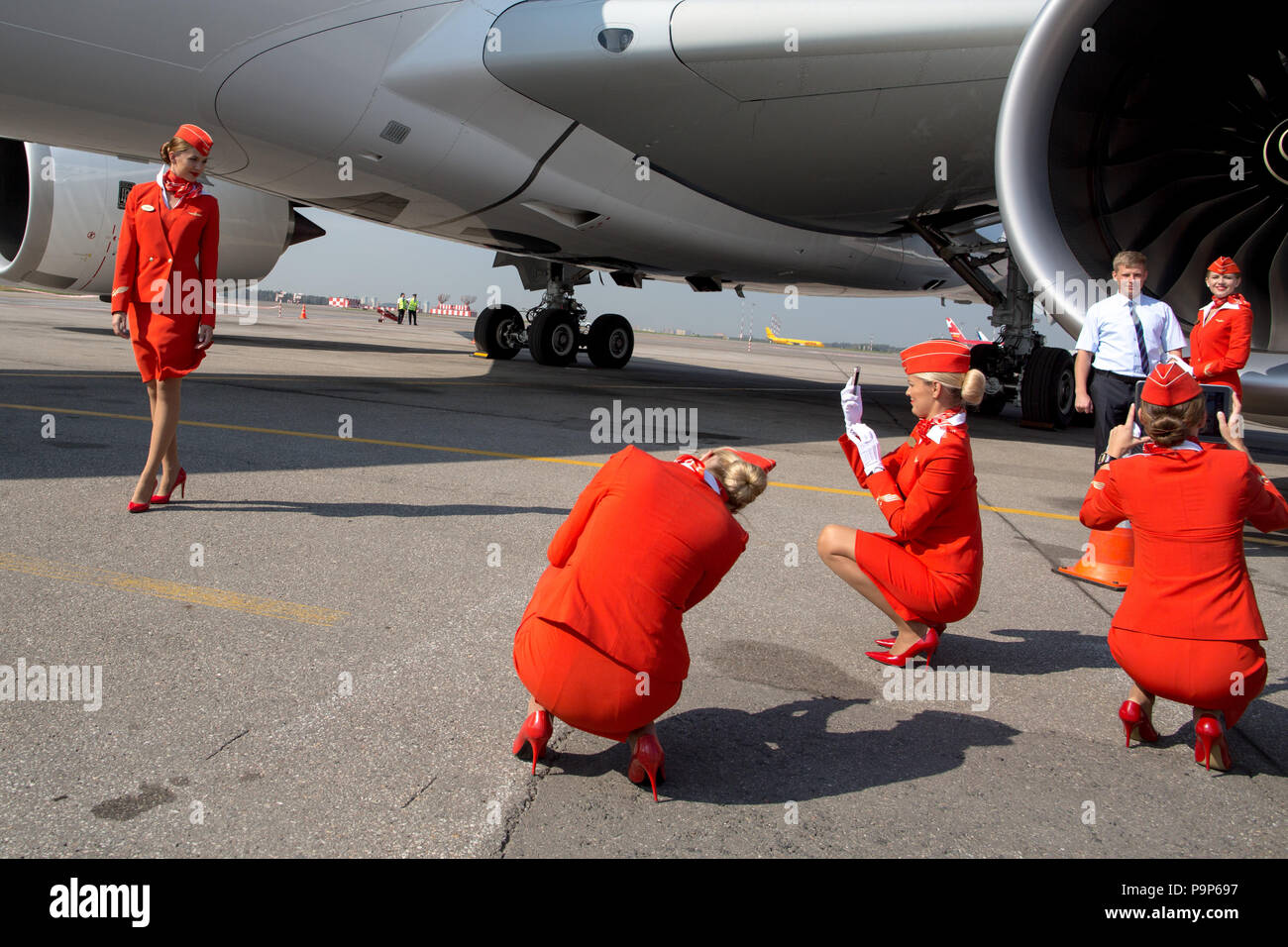 Aeroflot's flight attendants pose for photos near the Airbus A350 civil jet airplane during its visit into Sheremetyevo airport, Moscow, Russia - Stock Image