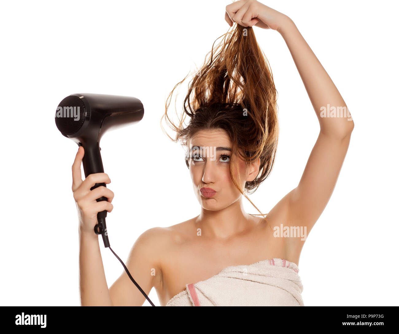 young beautiful woman drying her hair with a blow dryer on a white  background - Stock 17d6d82e7