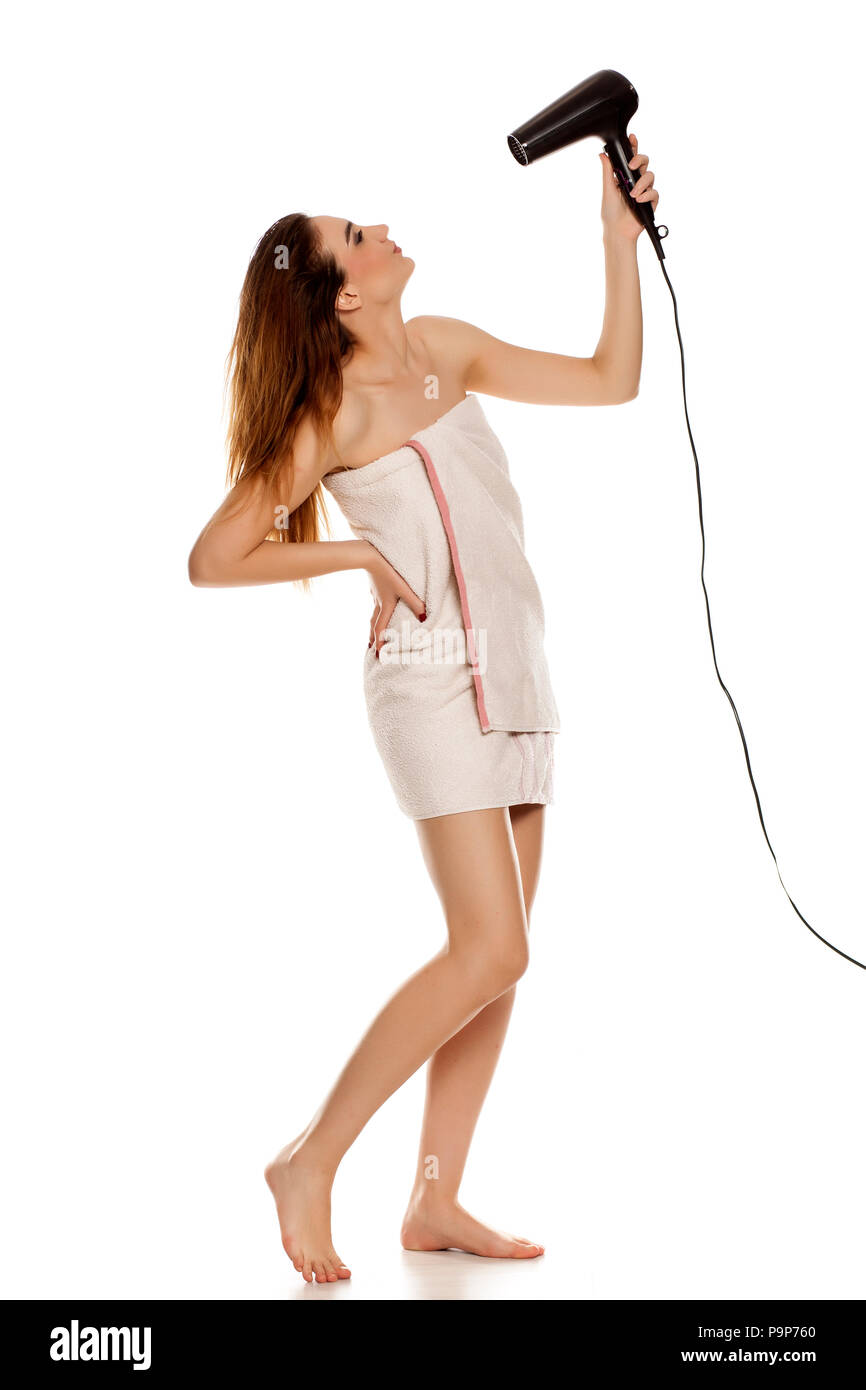 young beautiful woman drying her hair with a blow dryer on a white background - Stock Image