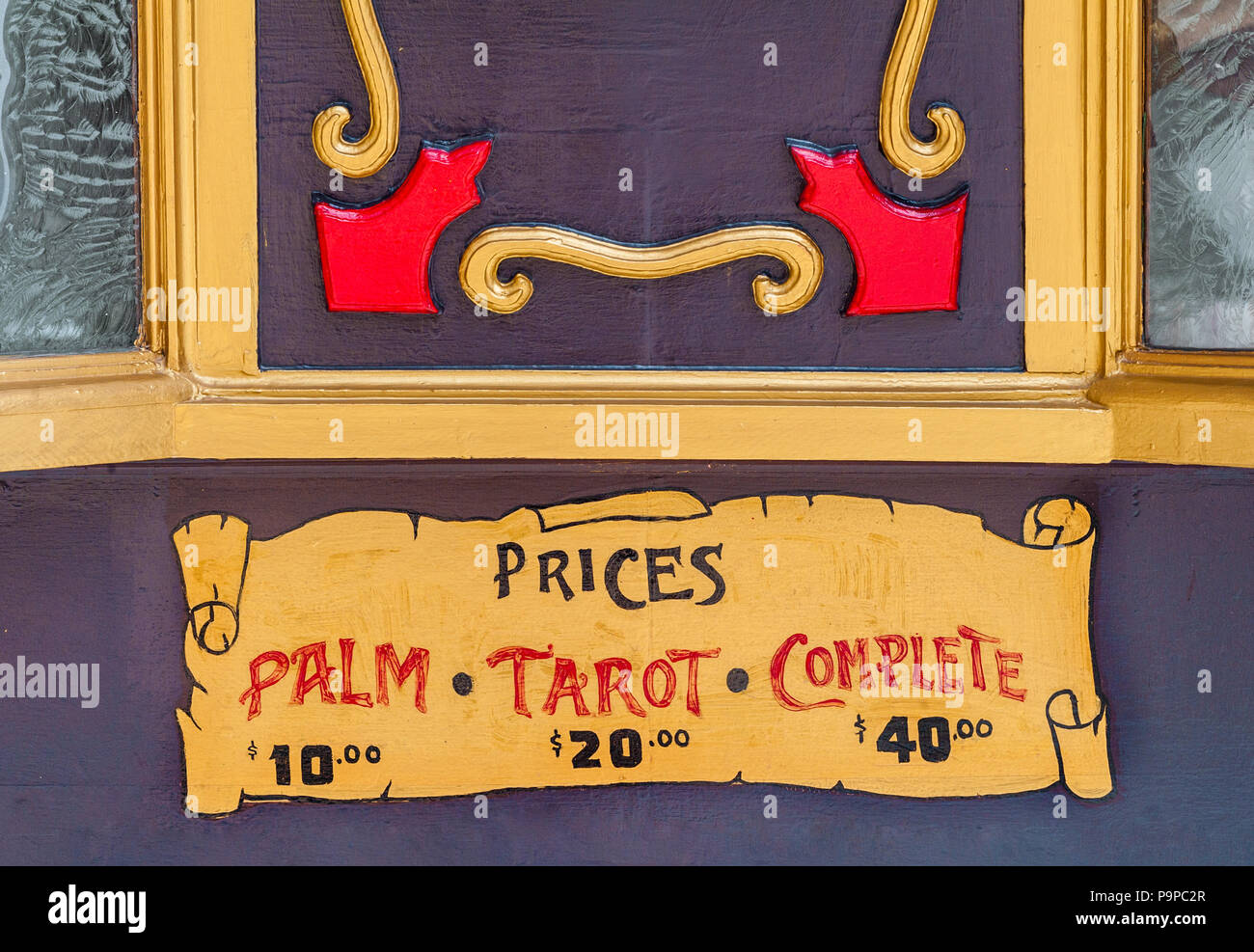 Close-up details of traveling carnival fortune teller or psychic sign with vintage lettering and old peeling paint. Colorful signage for a palm reader. - Stock Image