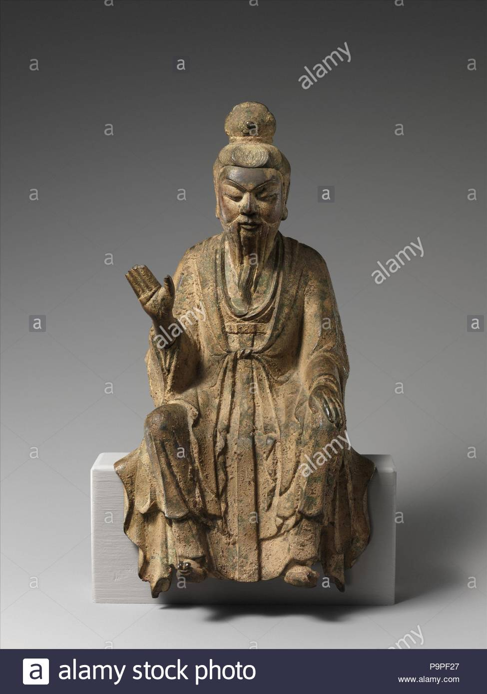 Daoist Immortal, probably Laozi (??), Five Dynasties period (907–60), 10th century, China, High-leaded bronze, H. 9 1/2 in. (24.1 cm); W. 4 1/2 in. (11.4 cm), Sculpture, This sculpture epitomizes the merging of religious and secular imagery in later Chinese Buddhist sculpture. With his shaven head and elongated earlobes, the figure resembles a luohan (one of the Indian disciples of the Buddha), but his refined facial features, dignified posture, long-sleeved robe, and pointed shoes—all attributes associated with Confucian scholar-officials—identify him unmistakably as a youthful monk. - Stock Image