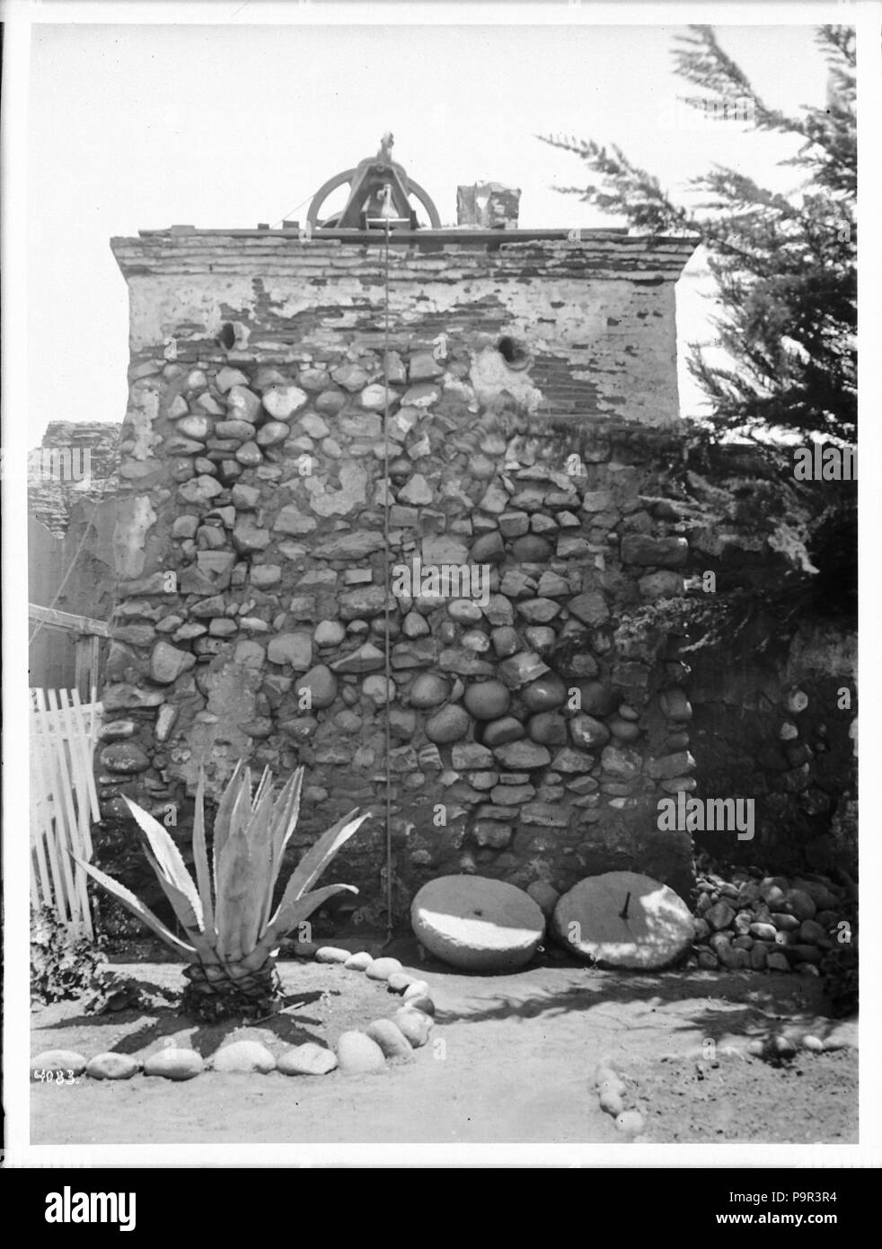 . English: Bell tower at San Diego Mission, ca.1905 Photograph of the bell tower at San Diego Mission, ca.1905. A rope attached to the bell(s) hangs down from a bracket at the top of the natural stone tower. Two disused millstones lay on the ground at the foot of the tower near a cultivated yucca-like plant which grows in a semicircle of stones. Part of a white picket fence is visible at left.  Call number: CHS-4083 Legacy record ID: chs-m16591; USC-1-1-1-14081 Photographer: James, George Wharton Filename: CHS-4083 Coverage date: circa 1905 Part of collection: California Historical Society Col - Stock Image
