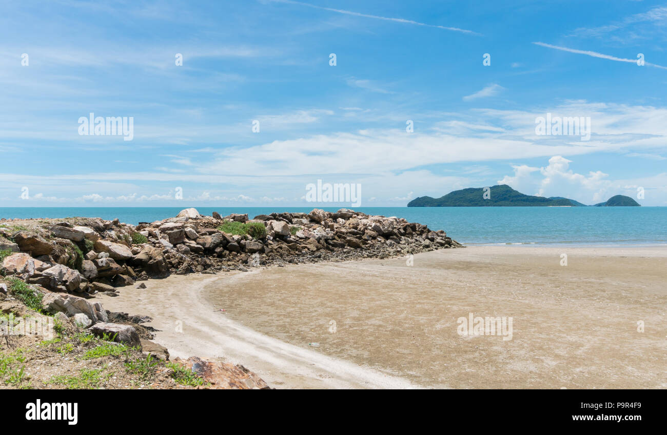 Rock or stone mound or pile on the beach at Prachuap Khiri Khan Thailand. Beach and sea or brine and blue sky and green tree mountain or hill.  Summer Stock Photo