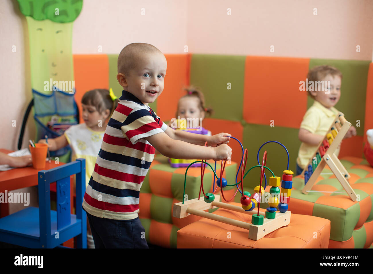 Group of children playing in kindergarten or daycare centre Stock Photo