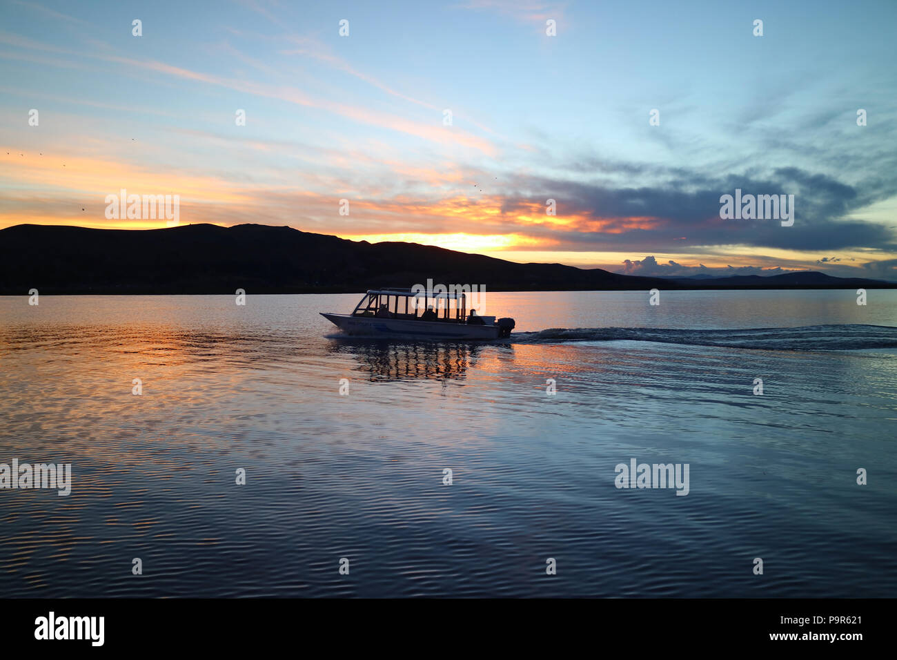Silhouette of a Cruising Boat on Lake Titicaca at Sunset, Puno, Peru, South America - Stock Image