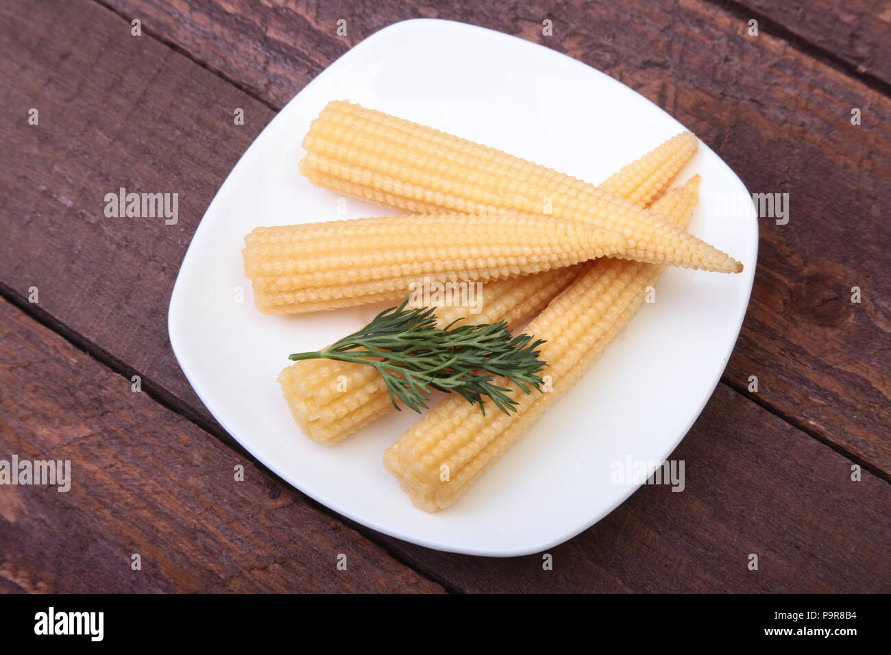 Mini Corn cob preserved on plate on wooden board. - Stock Image