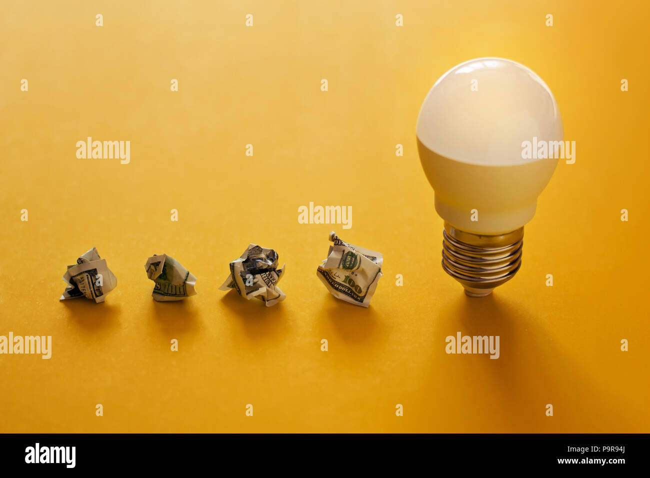 concept of energy saving. Lamp and crumpled dollar bills in a row on yellow background - Stock Image