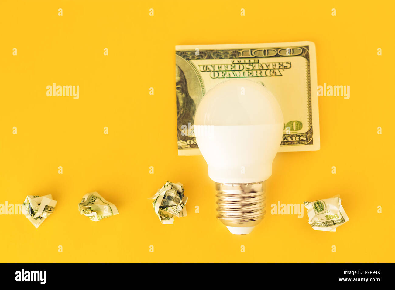 concept of energy saving. Energy saving light bulb on usd banknote and crumpled dollar bills in a row on yellow background - Stock Image