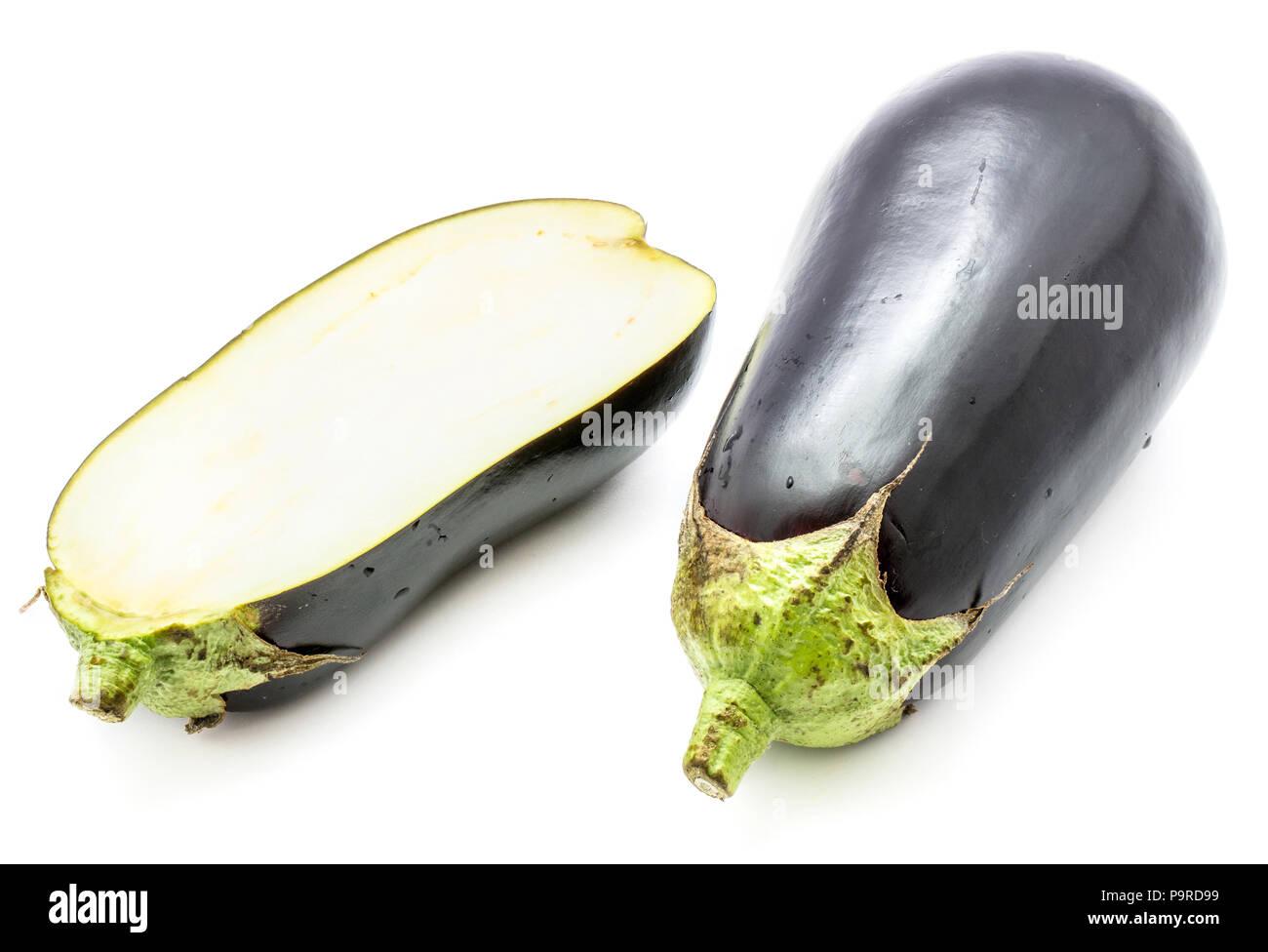 One whole and one half eggplant (aubergine), longitudinal section, isolated on white background - Stock Image