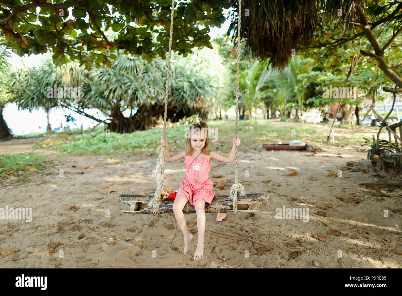 Little beautiful girl riding on swing on sand background, wearing pink dress. - Stock Image