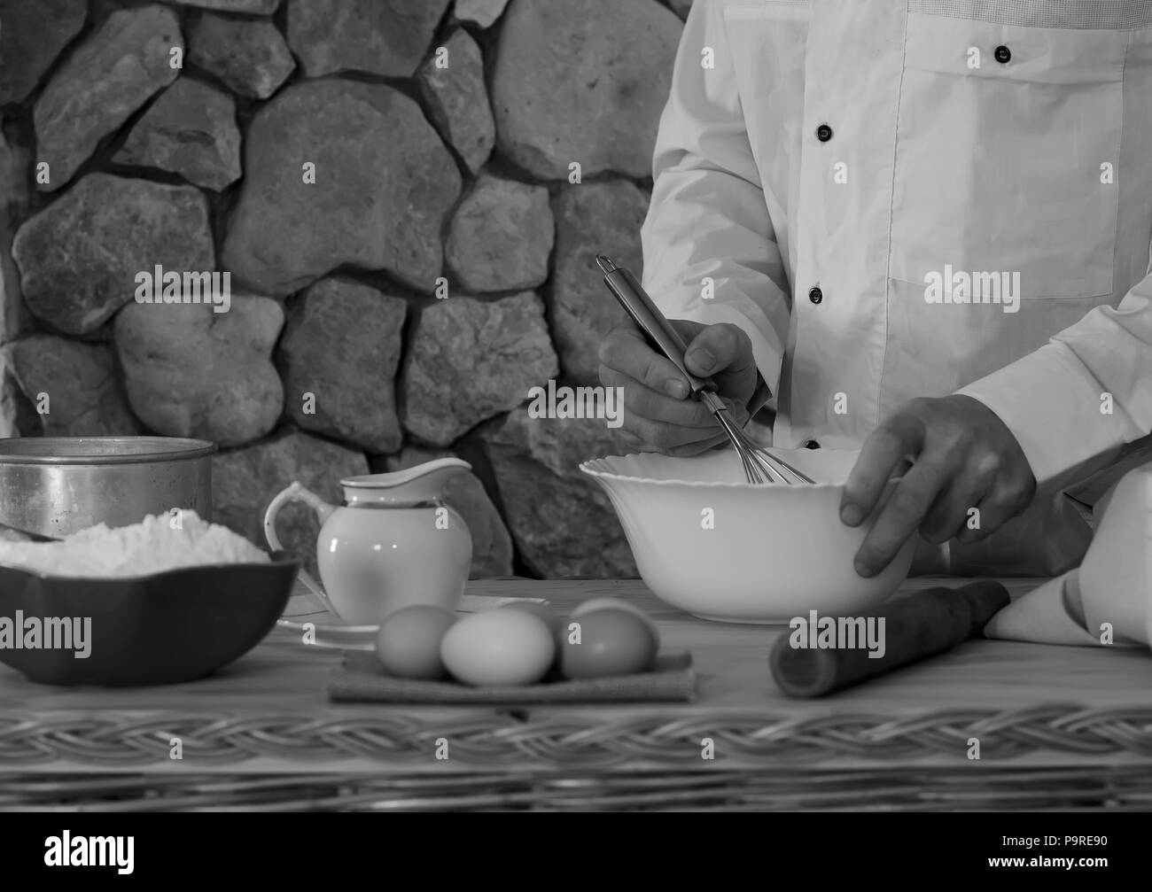 bowl with flour, eggs, a sieve and a mortar, and a male cook in a white garment whisk the whisk the batter. Concept of rustic kitchen, selective focus - Stock Image