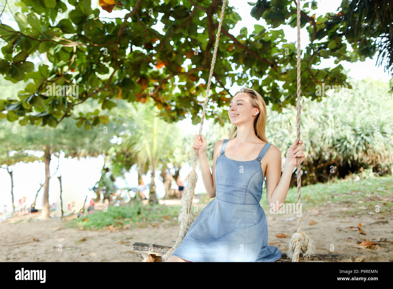 Young nice woman wearing jeans dress and riding on swing, sand in background. - Stock Image