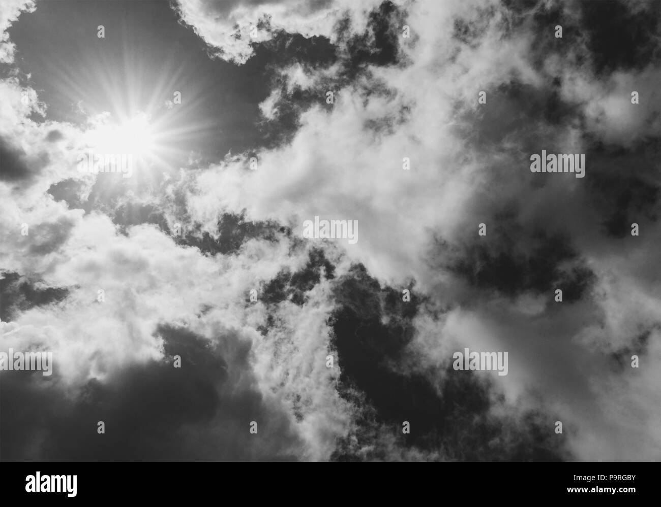 bright sun is closed by clouds, black and white photo - Stock Image