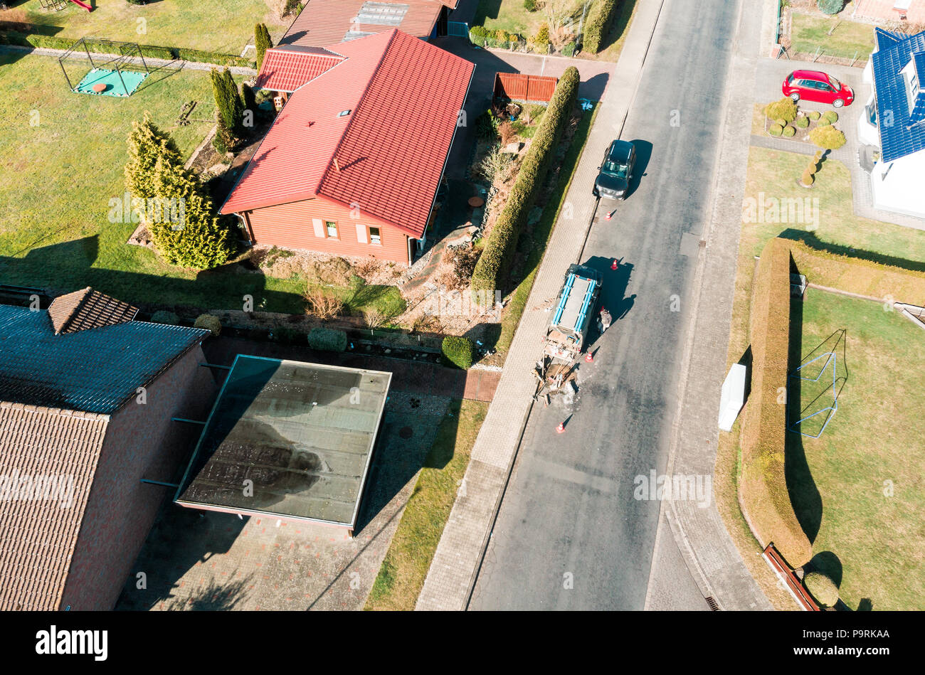 Aerial view of a simple detached house on an asphalted grey village road, on which a road worker carries out maintenance work, made with drone Stock Photo