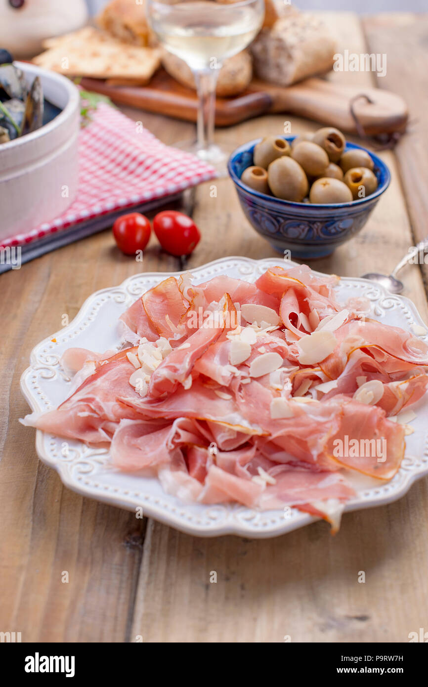 Plate with meat on a wooden background, green olives. - Stock Image