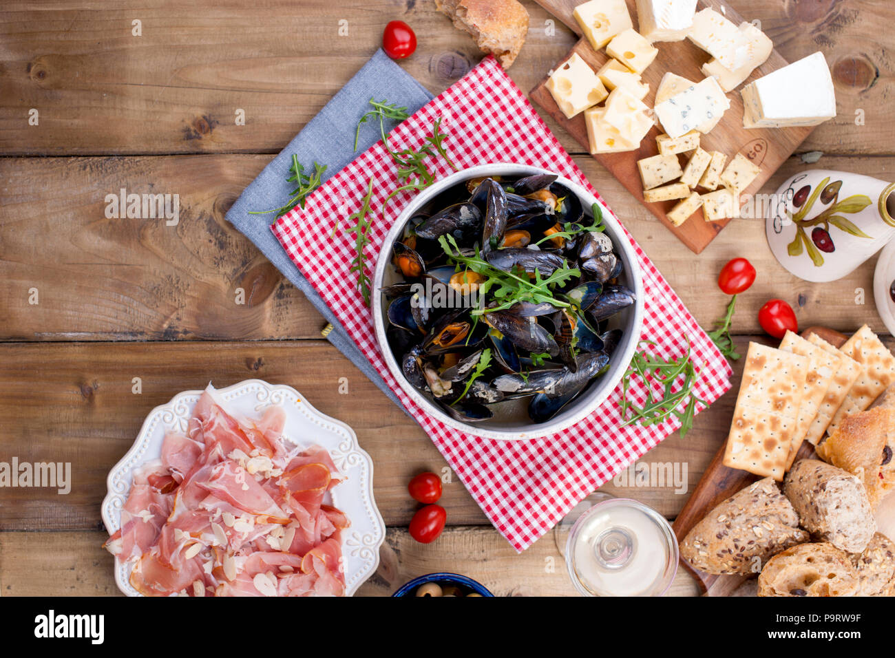 Muesli in a white ceramic bowl, on a red napkin. Cheese on a wooden board and a glass of white wine, olives, bread. Meat on a plate. On a wooden background. Free space for text or advertising - Stock Image