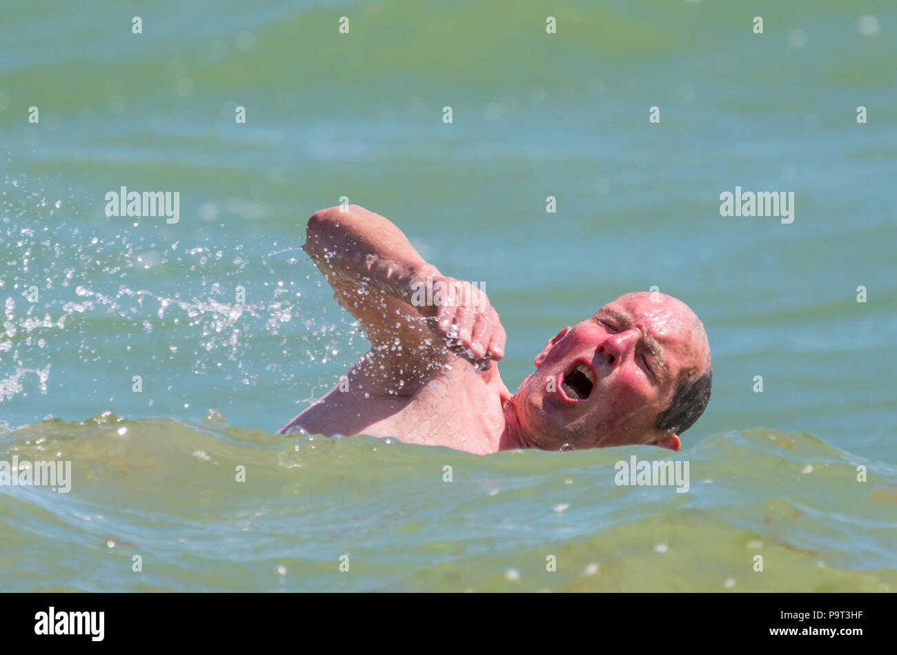 Man swimming in the sea in the UK with his head out of the water taking a breath. Man swimming in the ocean. - Stock Image