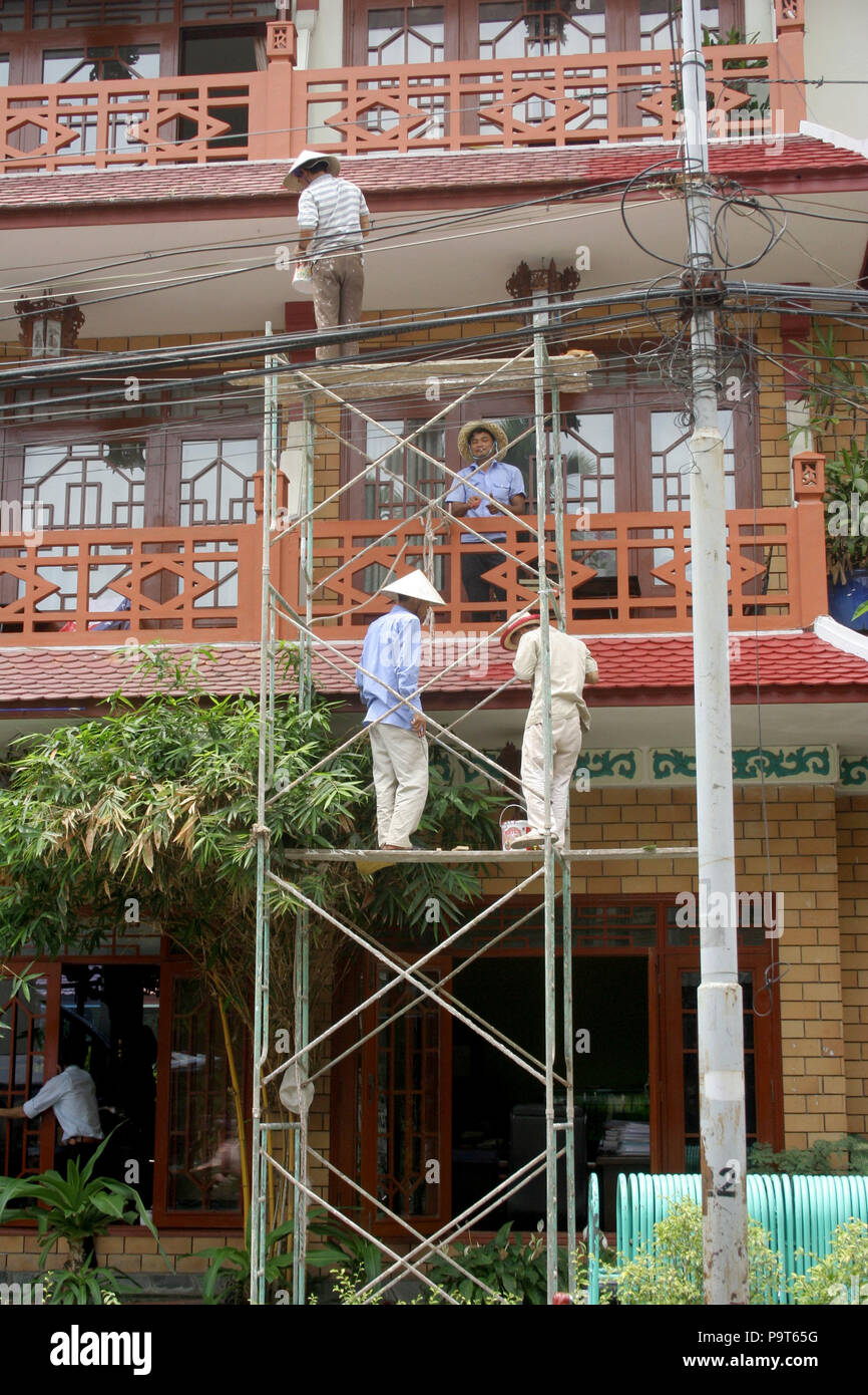 5290da8aa07 Vietnamese Men in Conical Hats Standing on Scaffolding Painting a Hotel in  Hoi An
