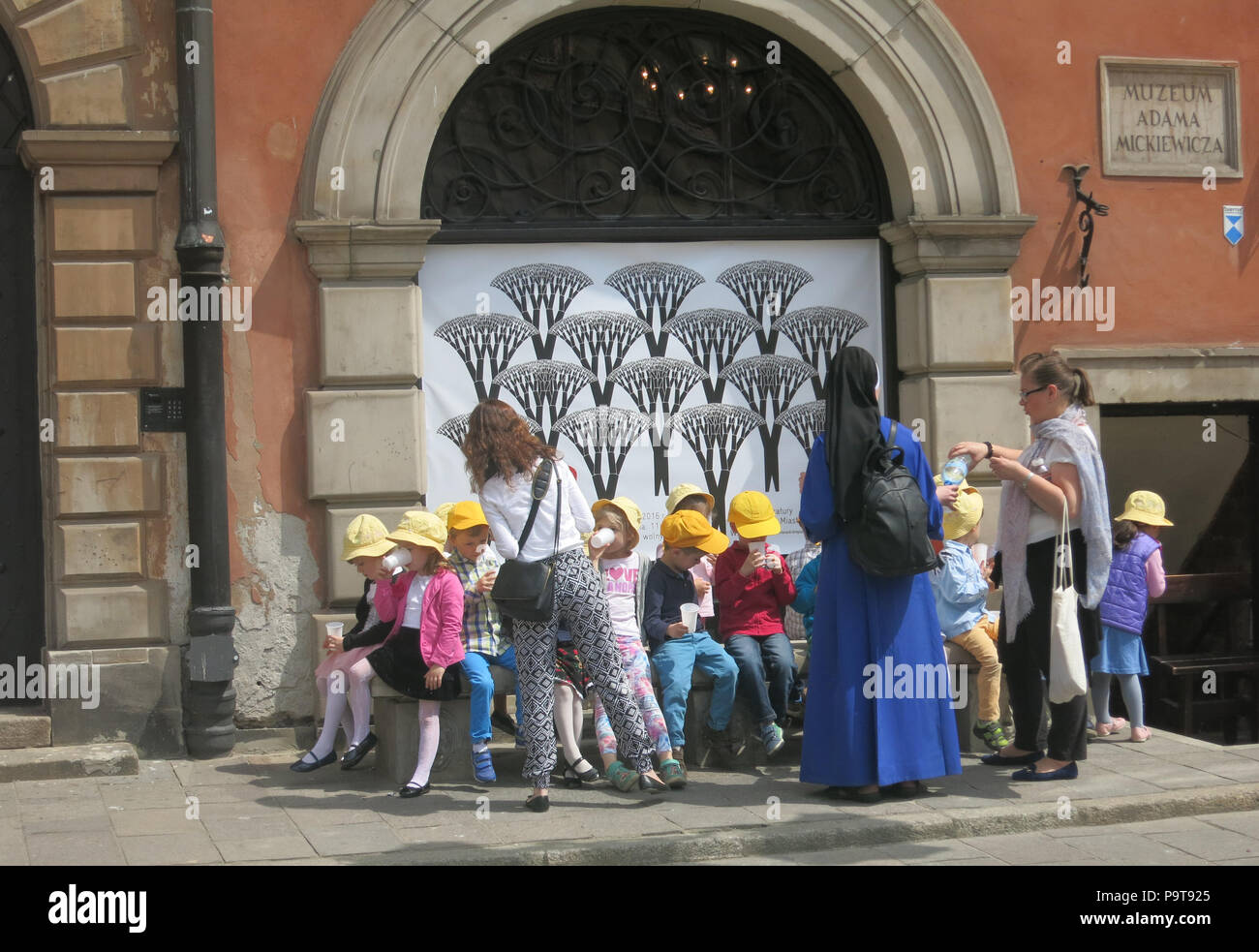 A group of schoolchildren before the Adama Mickiewicza museum,  visiting the old town, Warsaw, Poland - Stock Image
