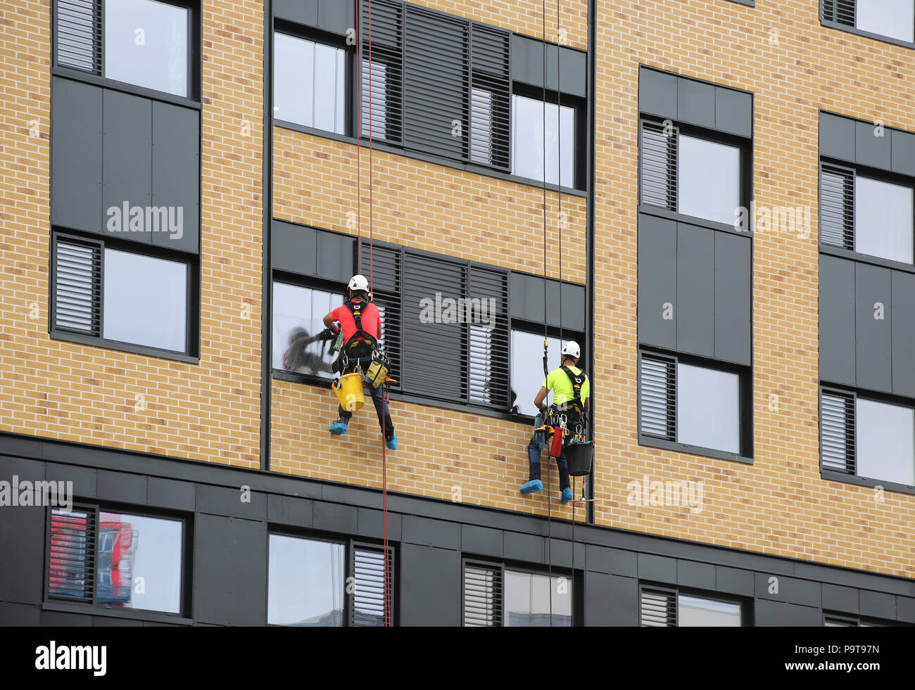 Two window cleaners use abseiling ropes to access windows on a new tower block in Portsmouth town centre, Hampshire, UK - Stock Image