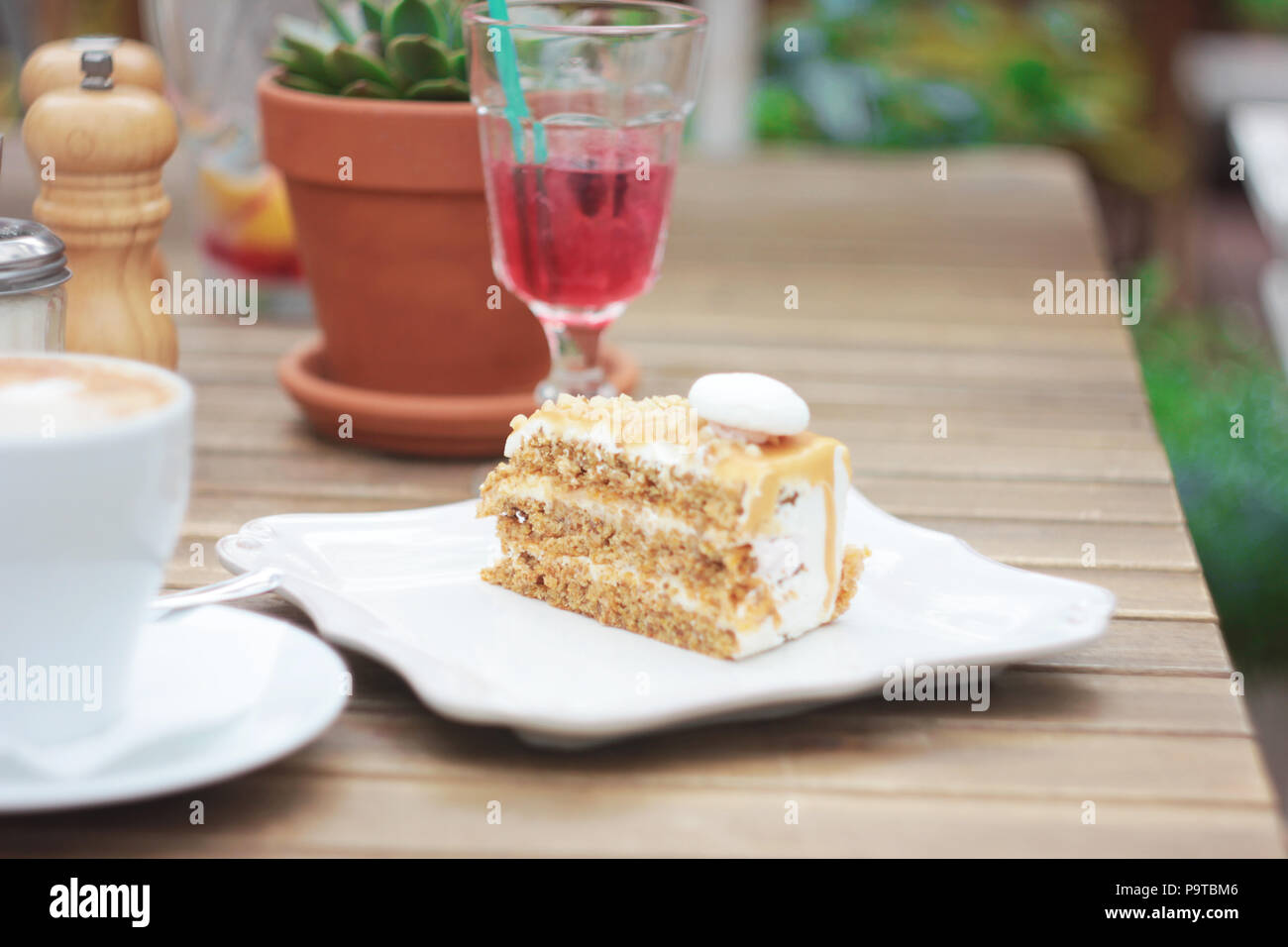 The piece of cake on table of summer terrace in cafe, picnic, set table - Stock Image