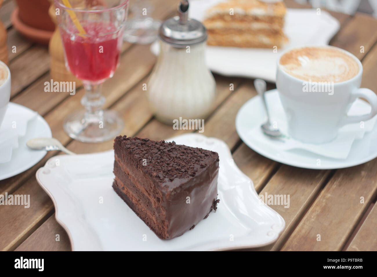 The piece of chocolate cake on table of summer terrace in cafe, picnic, set table - Stock Image