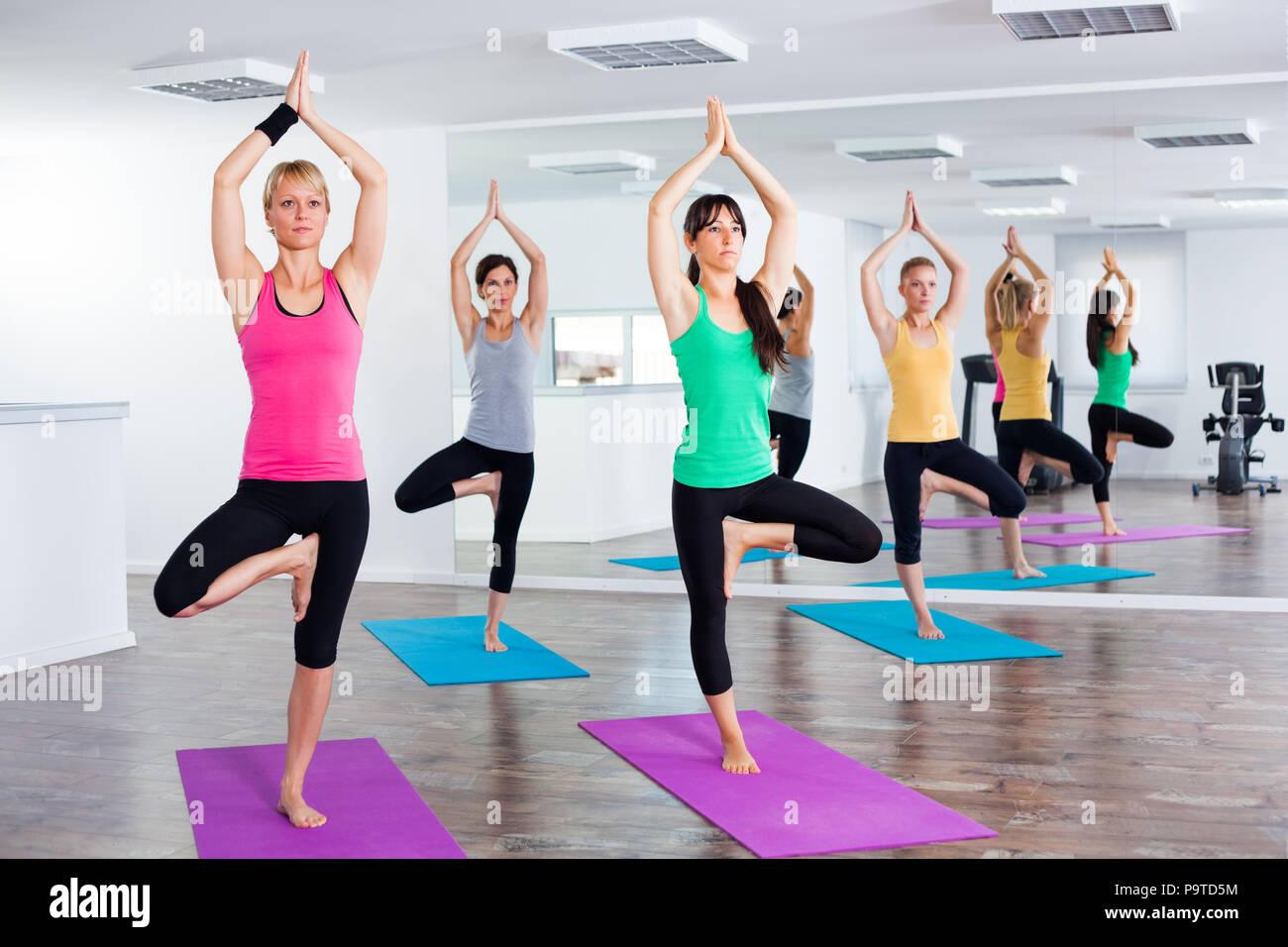 Four girls practicing yoga, Vrikshasana / Tree pose - Stock Image