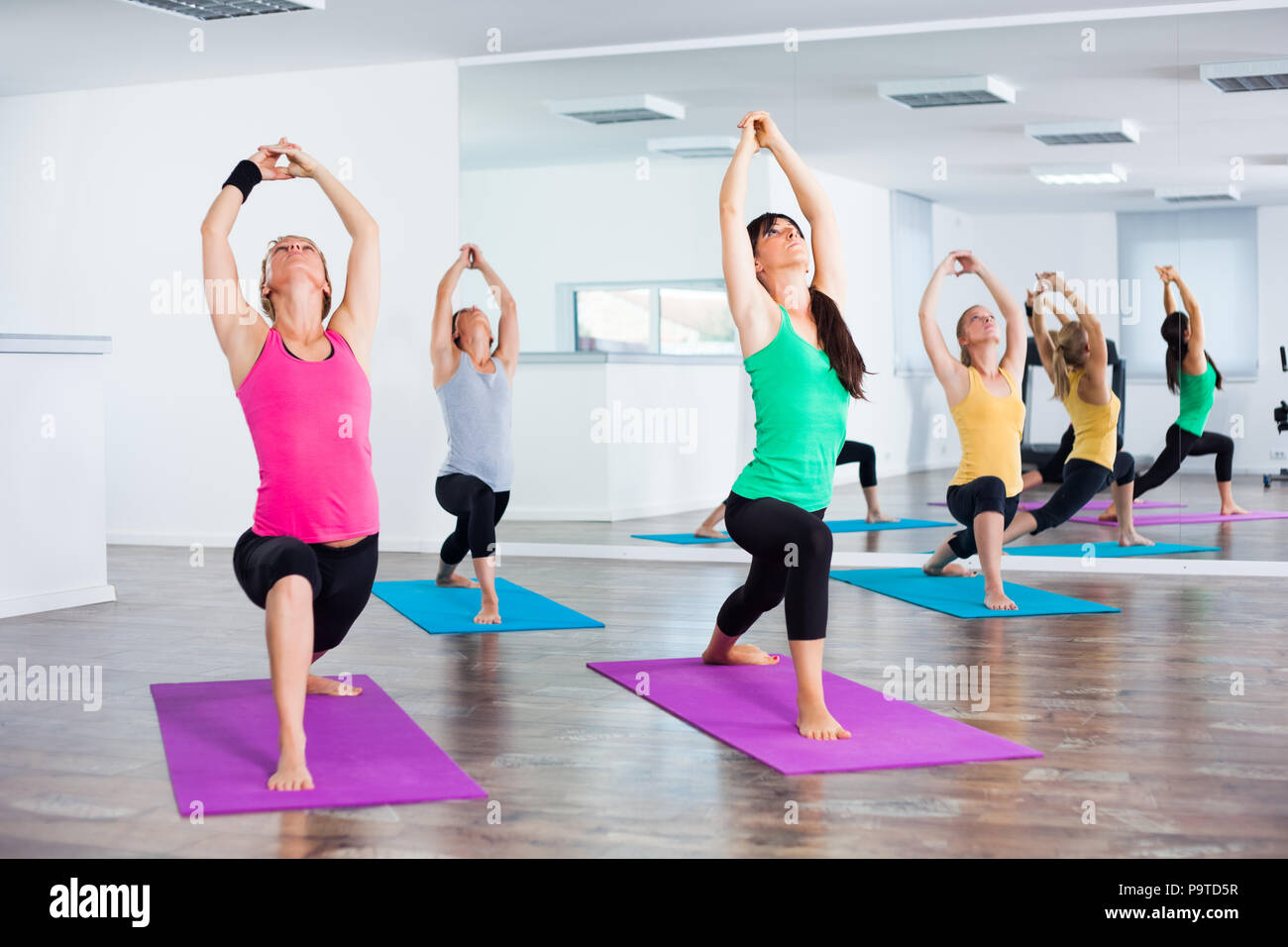 Four girls practicing yoga, , Virabhadrasana / Warrior pose - Stock Image