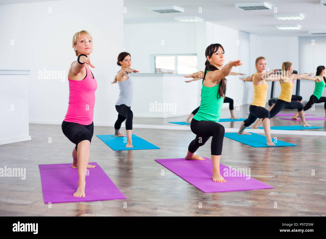 Four girls practicing yoga, Virabhadrasana / Warrior pose - Stock Image
