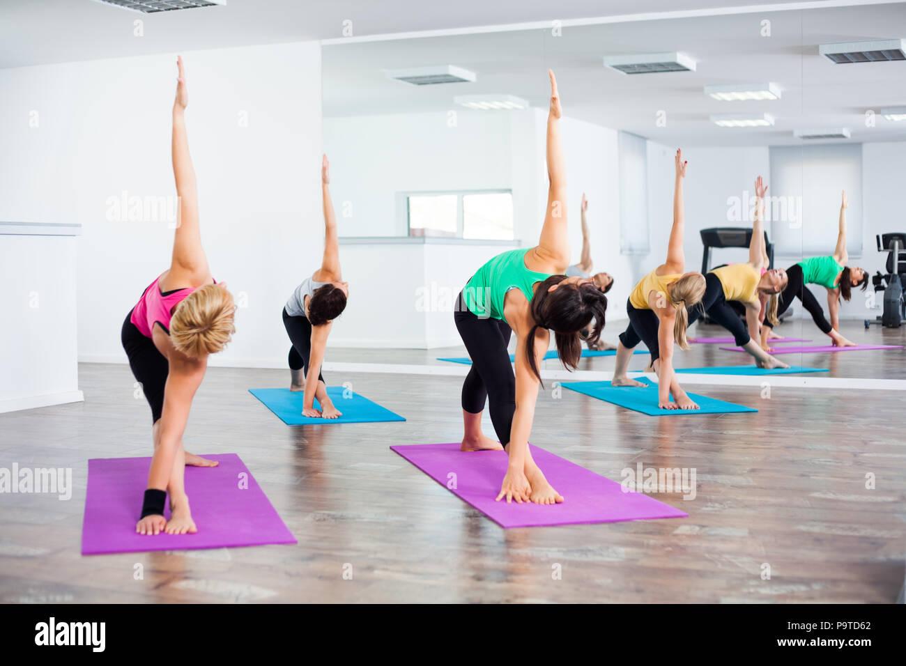 Four girls practicing yoga, Trikonasana / Bikram triangle right pose - Stock Image