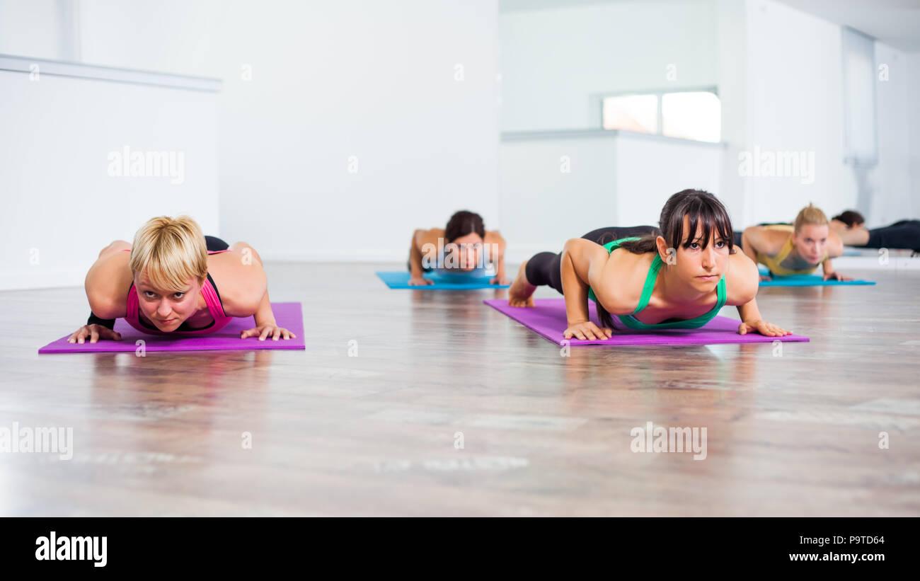 Four girls practicing yoga, Chaturanga Dandasana / Four Limbed Staff Pose - Stock Image