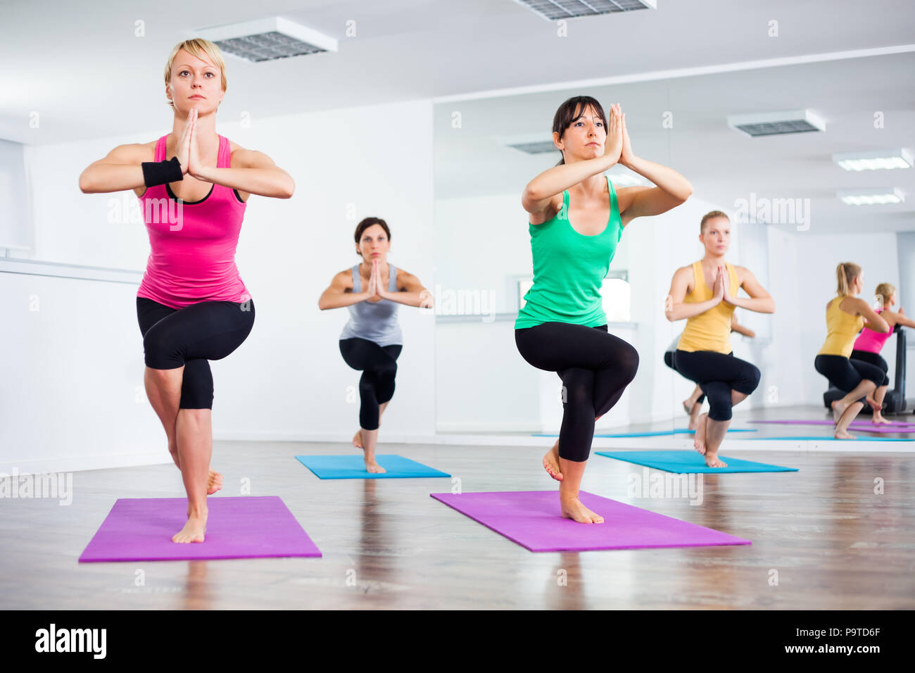 Four girls practicing yoga, Garudasana / Eagle Pose - Stock Image