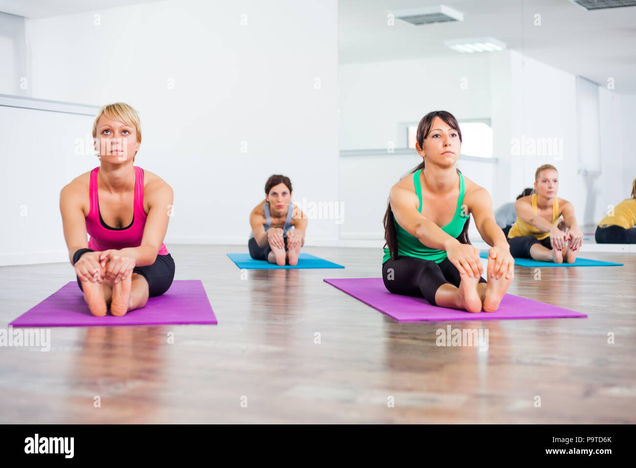 Four girls practicing yoga, Pascimottanasana / Seated Forward Bend pose - Stock Image