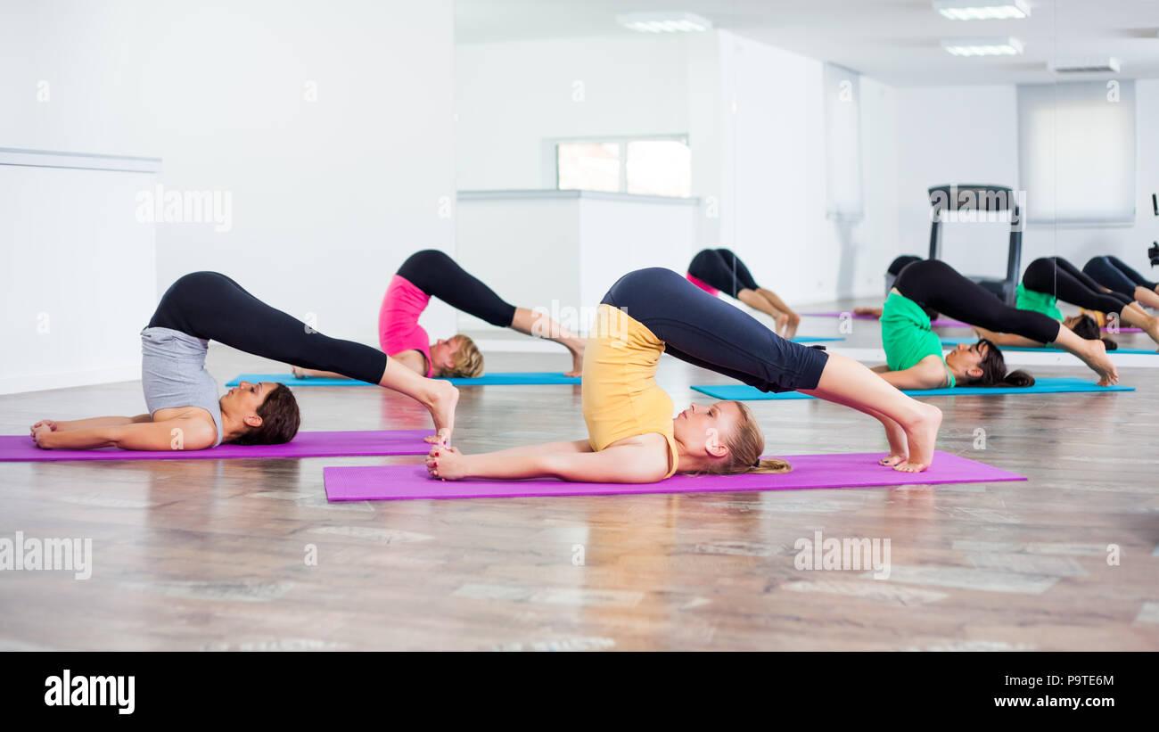 Four girls practicing yoga, Halasana / Plow pose - Stock Image