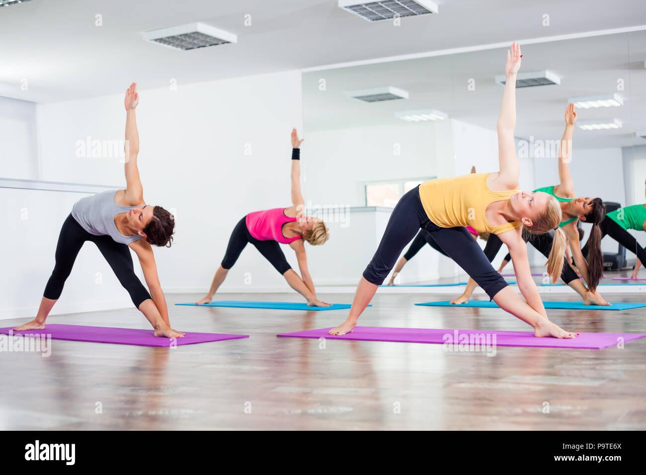 Four girls practicing yoga, Trikonasana / Bikram triangle left Stock Photo