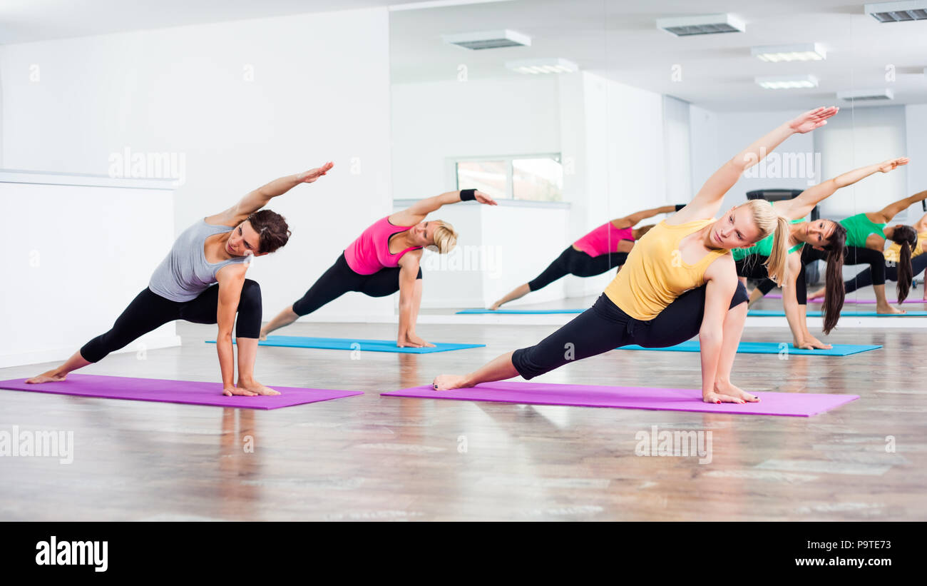Four girls practicing yoga, Vasisthasana / Half side plank pose - Stock Image
