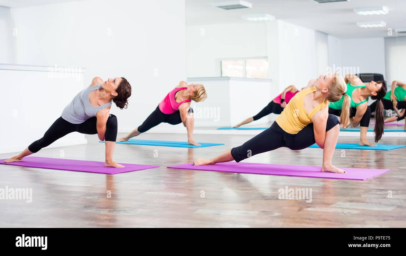 Four girls practicing yoga - Stock Image