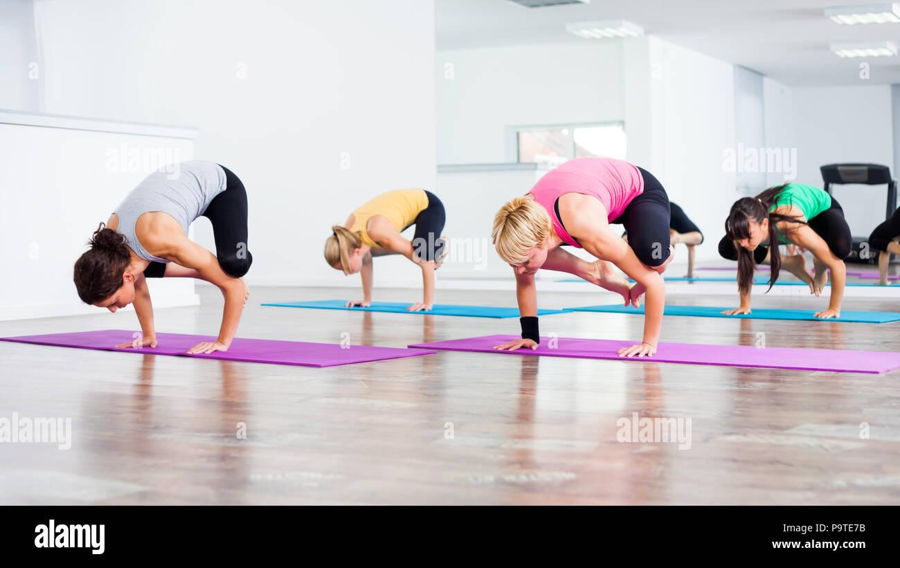 Four girls practicing yoga, Bakasana / Crane pose - Stock Image