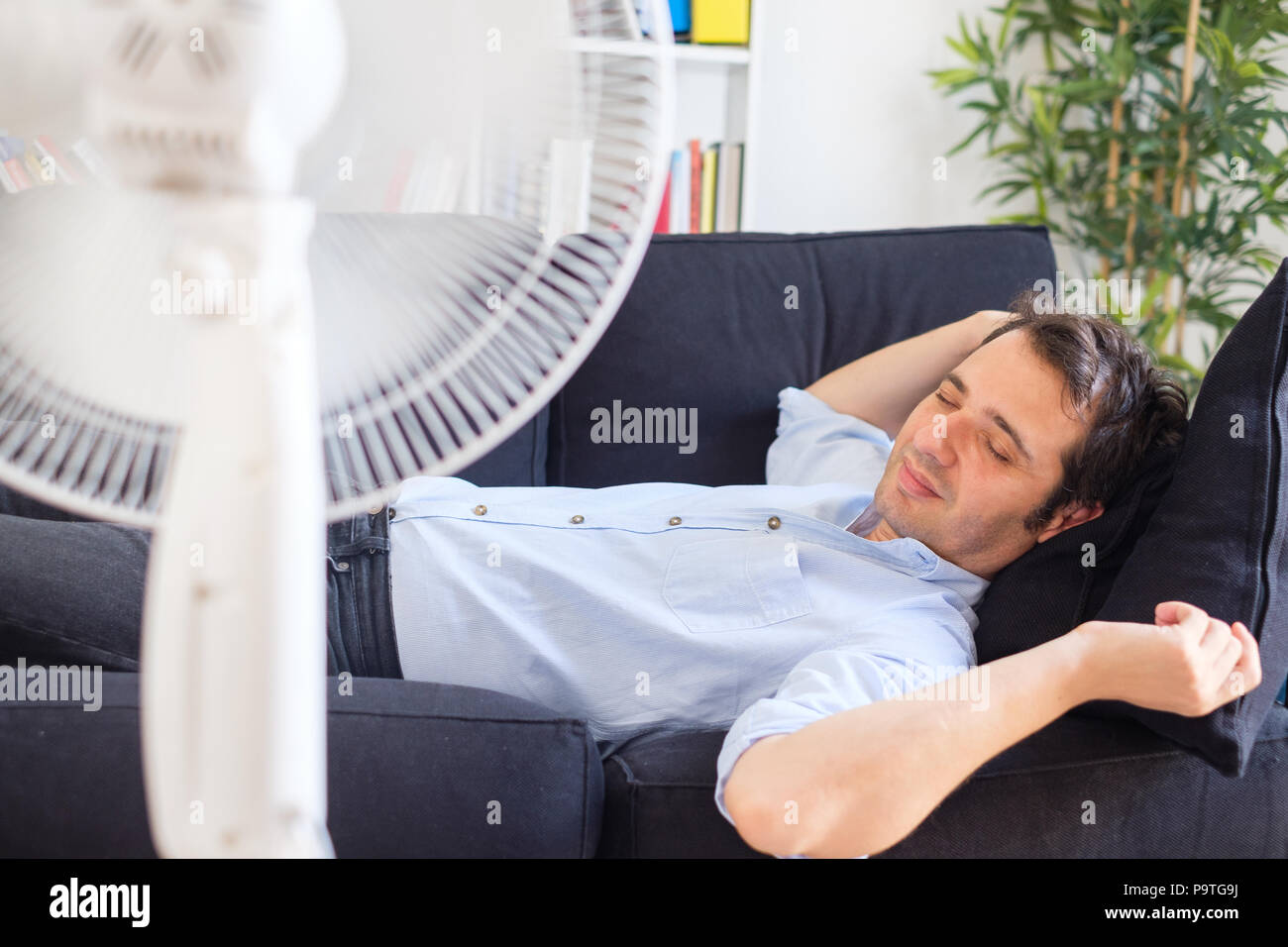 Man refreshing with electric fan against summer heat wave - Stock Image