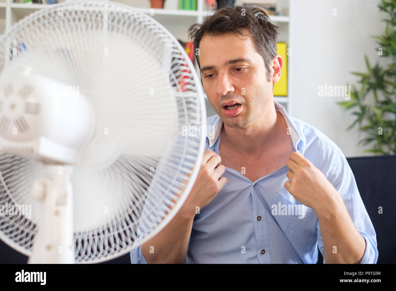 Man sweating and trying to refresh in summer haze - Stock Image