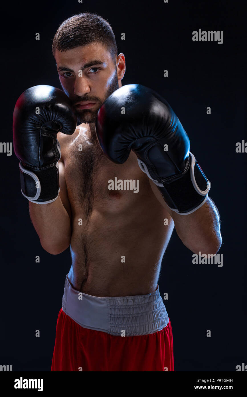 Double arm block. Boxing trainer showing defensive techniques. Combat sport, fight club. Studio shot on a black background - Stock Image